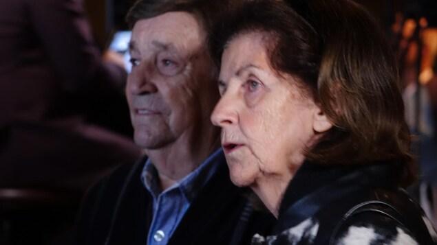 Un homme et une femmes âgés regardent la défaite de leur parti sur deux écrans géants.