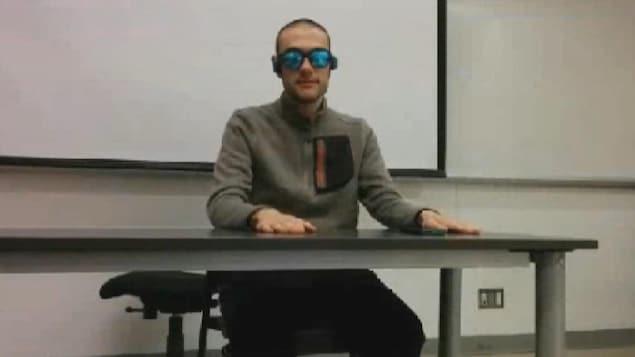 Un homme avec des lunettes soleil et des écouteurs assis à une table.