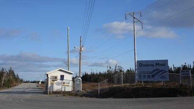 L'entrée de la mine Donkin au Cap-Breton avec une affiche et un grillage.
