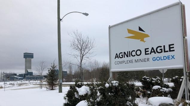 L'affiche à l'entrée du site minier Goldex, d'Agnico Eagle, avec la mine au loin.