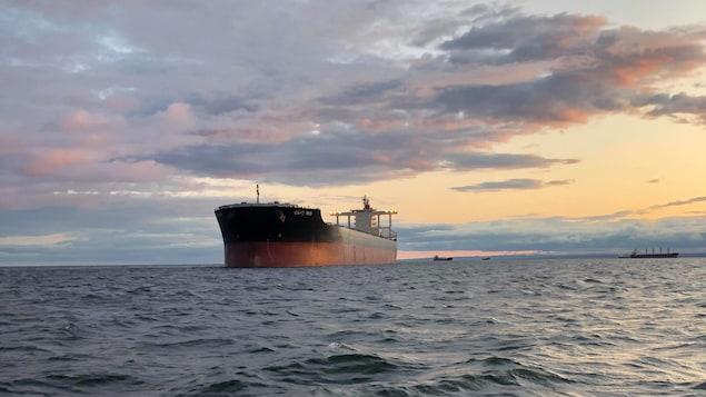 Un minéralier sur l'eau au coucher du soleil