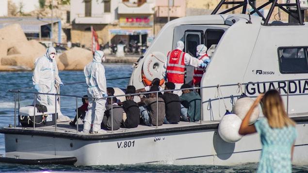 De jeunes hommes sont assis sur le pont d'un petit bateau, entourés de gens vêtus de masques et de combinaisons qui les couvrent des pieds à la tête.