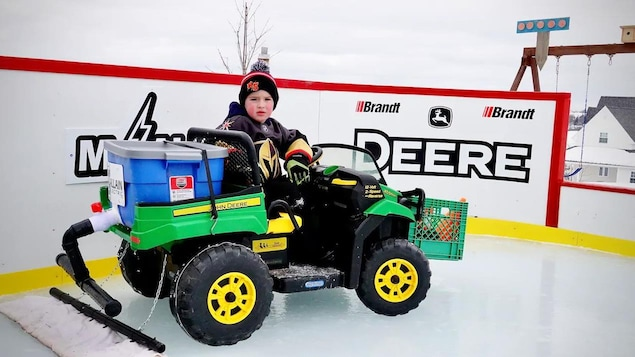 Un jeune garçon sur une mini Zamboni, sur une patinoire extérieur.