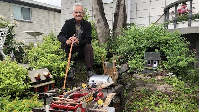 Un homme devant une scierie miniature.
