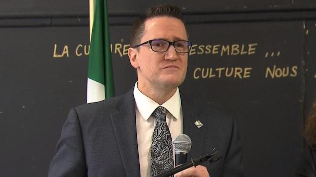 Benoit Charette, tenant un micro, en conférence de presse.