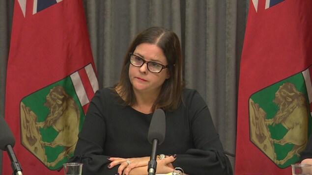 La ministre Stefanson est assise devant deux drapeaux du Manitoba et est habillée de noir.