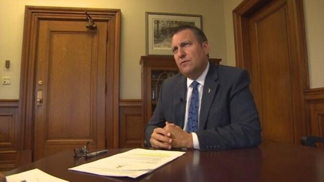 Le ministre assis sur une table avec des documents devant lui.