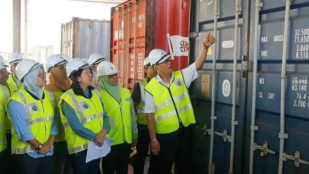Le ministre malaisien de l'Environnement, Yeo Bee Yin (devant, 2e à gauche), et des fonctionnaires inspectent un conteneur contenant des déchets plastiques le 20 janvier 2020 avant de le renvoyer dans les pays d'origine à Butterworth.