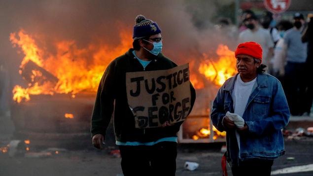 Deux hommes, dont l'un porte un masque et tient une pancarte près d'un véhicule en feu.