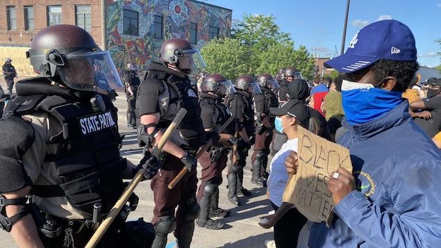 Des policiers antiémeute forment une ligne devant des manifestants. Un homme tient une pancarte où on peut lire : «Black lives matter».
