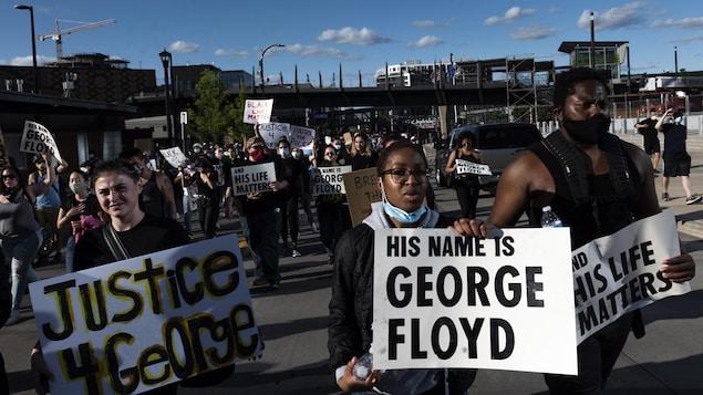 Des manifestants brandissent des pancartes dans une rue de Minneapolis.