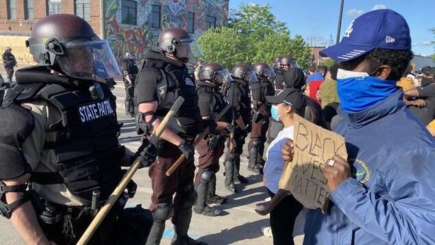 Des policiers antiémeute forment une ligne devant des manifestants placés devant eux. Un homme tient une pancarte où on peut lire : «Black lives matter».