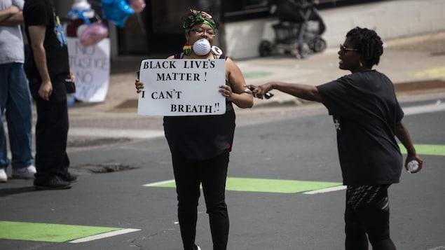 Une femme manifeste en tenant une pancarte sur laquelle il est écrit: «Black Lives Matter! I can't breath».