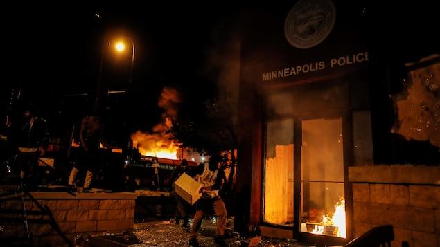 Un manifestant lance une caisse à l'intérieur d'un poste de police en feu en pleine nuit à Minneapolis.