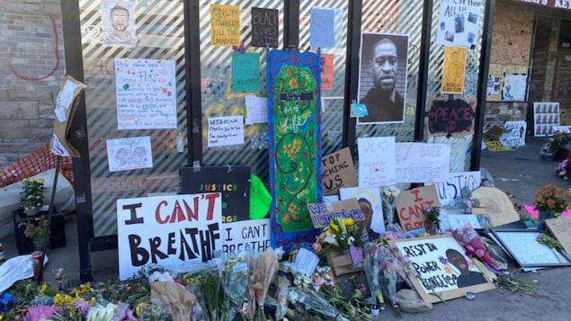 Des pancartes et des fleurs en hommage à l'homme noir de 46 ans, dont la photo a été collé sur un mur.