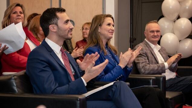 Le ministre de l'Éducation Stephen Lecce, la ministre des Affaires francophones Caroline Mulroney et le président par intérim de Groupe Média TFO, Éric Minoli, dans une foule, assis sur des fauteuils, applaudissent lors d'un événement.
