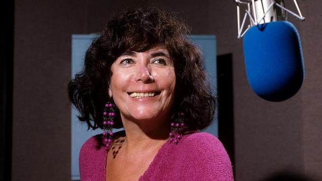 Minou Petrowski posant près d'un micro dans le studio 22 de la Maison de Radio-Canada.