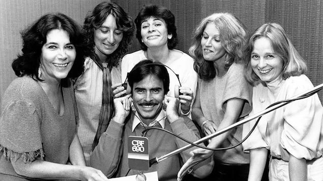 Dans un studio de radio, l'animateur Normand Séguin (assis au centre) entouré des chroniqueuses Minou Petrowski, Suzanne Giguère, Louise Saint-Pierre, Cécile Rodrigue et Élizabeth Gagnon. Micro avec logo CBF 690.