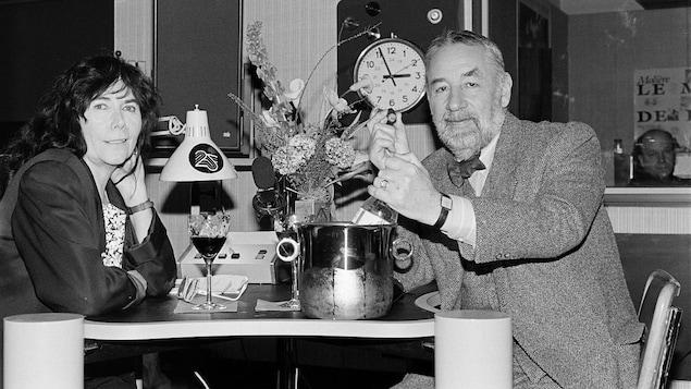 Minou Petrowski en studio radio avec Philippe Noiret, un cigare à la main. Sur la petite table, un bouquet de fleurs et du vin.