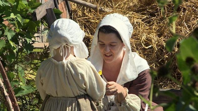 Une femme et un enfant en costumes du 18e siècle pendant un tournage.