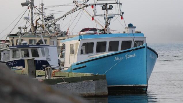 Un bateau de pêche peint en bleu et baptisé Miss Janet est amarré au quai.