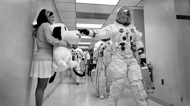 Le commandant de la mission Apollo 10, Thomas Stafford, dans son habit de cosmonaute marche dans un long corridor.