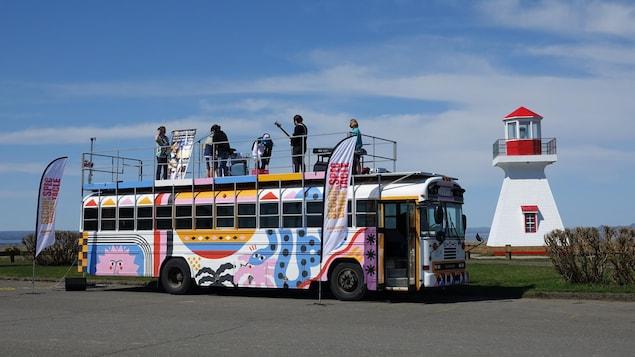 Des jeunes musiciens sur le toit d'un autobus stationné près d'un phare.