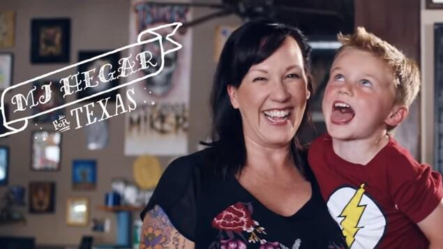Mary Jennings Hegar, dont on voit les tatouages, tient l'un de ses enfants dans ses bras.