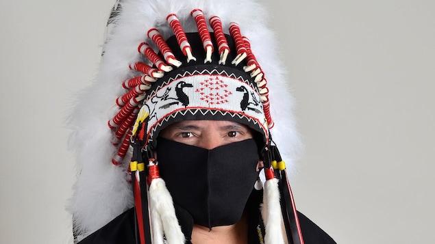 Un gros plan sur Garrison Settee. Il est vêtu d'un habit traditionnel et d'une coiffe autochtone.