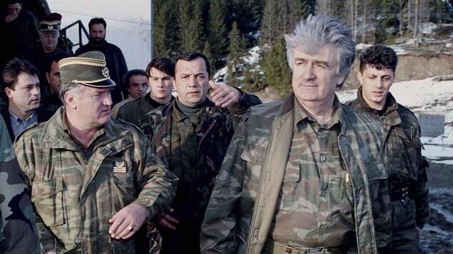 Des homme en tenue militaire marchent à l'extérieur.
