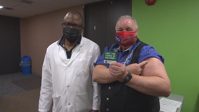David Chartrand est pris en photo avec un certificat indiquant «j'ai reçu le vaccin contre la COVID-19», accompagné d'un médecin.