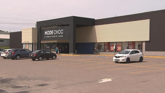 Quelques voitures sont garées dans le stationnement d'un magasin Mode Choc.