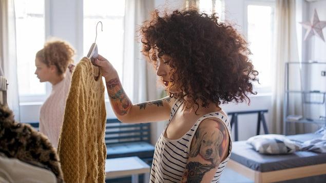 Une femme tient un pull sur un cintre.