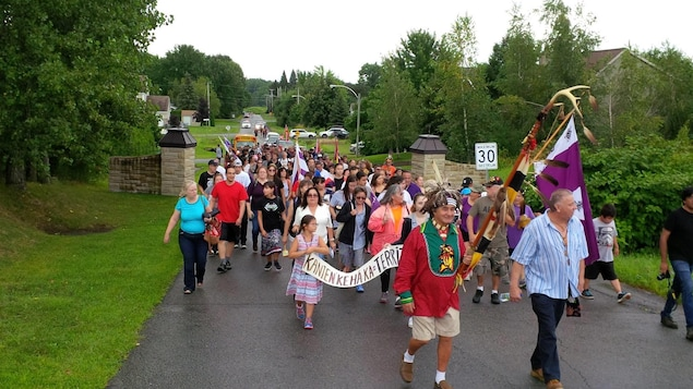 Un groupe de Mohawks de Kanesatake marchent en protestation contre le projet immobilier du Domaine des Collines d'Oka, le 12 août 2017.