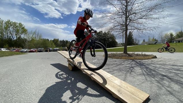 Un jeune traverse une planche sur son vélo.