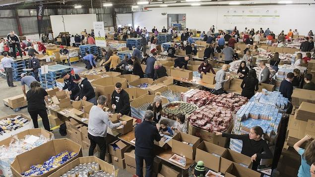 Plusieurs personnes devant d'énormes boîtes remplies de denrées.