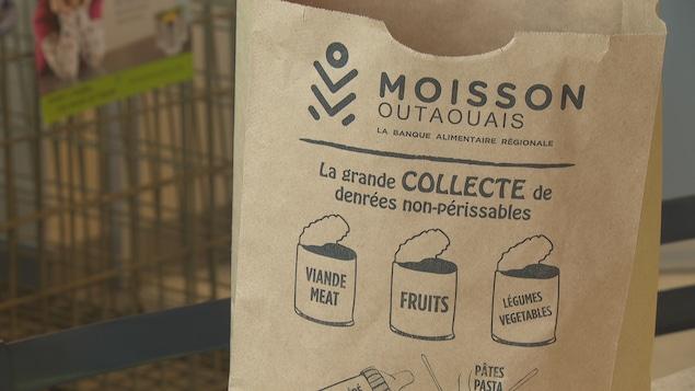 Un sac en papier brun avec le logo de Moisson Outaouais.