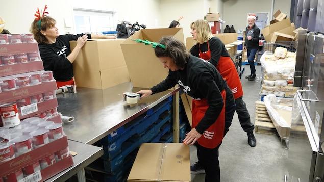 Trois bénévoles posent du ruban adhésif sur les fonds des boîtes en carton.