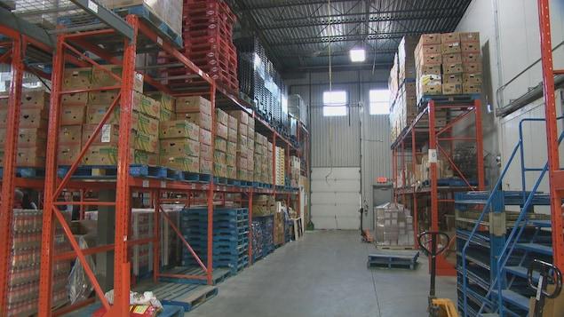 L'entrepôt de Moisson Outaouais, avec des étagères et des boites.