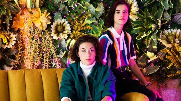 Les deux jeunes femmes sont assises côte à côte sur un sofa de couleur moutarde avec des fleurs derrière.