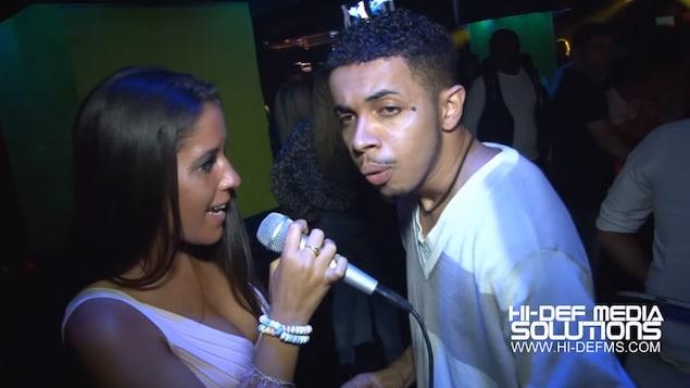 Une femme passe un homme en entrevue à la caméra.