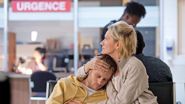 La femme et le jeune homme sont assis dans une salle d'attente, elle le tient dans ses bras.
