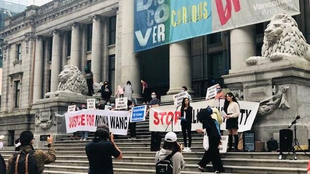 Des manifestants brandissent des banderoles sur les marches du musée.