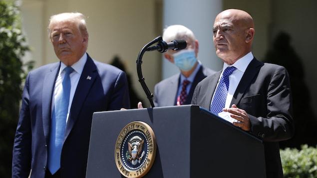 Le Dr Moncef Slaoui, devant un lutrin sur lequel se trouve un microphone, s'adresse aux reporters depuis la Roseraie de la Maison-Blanche, avec le président Trump à ses côtés.