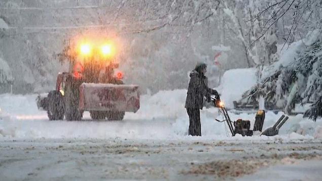 Un homme pousse une souffleuse à neige.