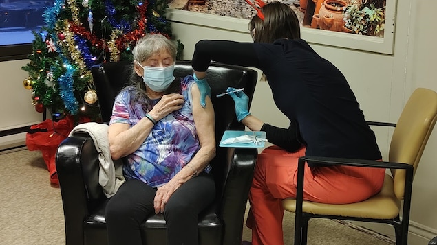 Une personne âgée, assise dans un fauteuil, reçoit un vaccin d'une professionnelle de la santé.