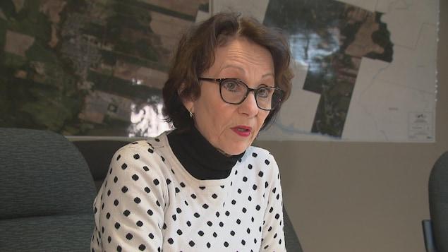 Une femme dans la cinquantaine accorde une entrevue à Radio-Canada. Elle porte un chandail à pois.