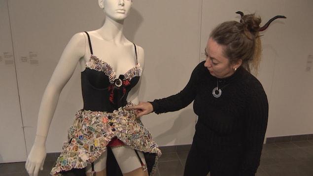 Monique Martin désigne des timbres cousues sur sa robe.
