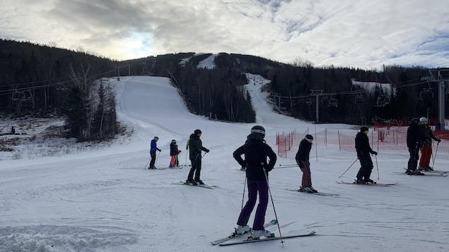 Des skieurs en bas de la montagne.