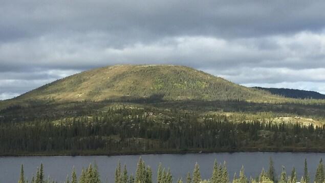 Une montagne se trouve au pied d'un lac, dans un milieu reculé et sauvage.